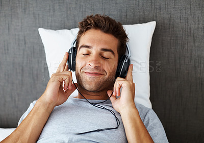 Buy stock photo Shot of a young man lying on the bed at home and listening to music on headphones