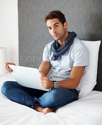 Buy stock photo Portrait of a confident young man sitting on his bed with laptop