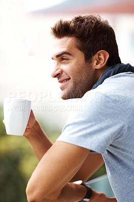 Buy stock photo Shot of a handsome young man enjoying a cup of coffee