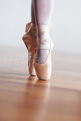 Buy stock photo Low angle shot of a dancer in ballet shoes dancing in Pointe on wooden floor