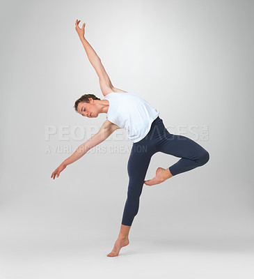 Buy stock photo Full length of a male ballet dancer performing a balancing act against white background
