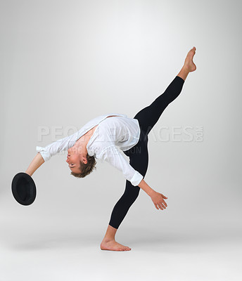 Buy stock photo Full length of a male ballet dancer performing a unique step with hat in hand against white - copyspace