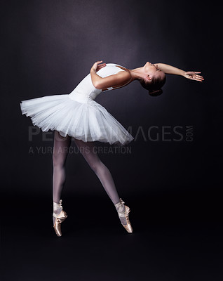Buy stock photo Full length of a teenage ballerina performing against black background