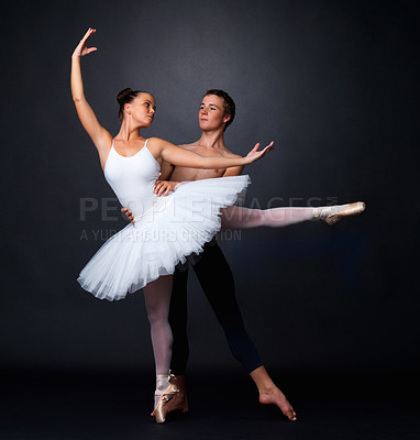 Buy stock photo Full length of two graceful ballet dancers performing against black background