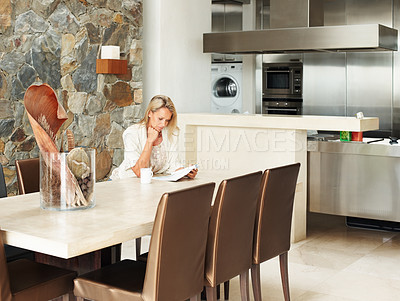Buy stock photo Mature woman reading book in dining room by kitchen in a modern house
