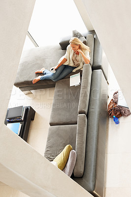 Buy stock photo Topview of a woman relaxing on a couch in a modern minimalist style home