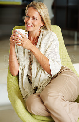 Buy stock photo Portrait of an attractive woman smiling over a thought with a cup of tea