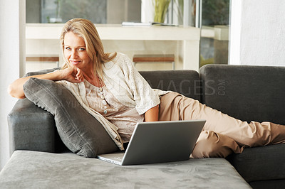 Buy stock photo Portrait of a happy pretty woman lying on sofa while using laptop