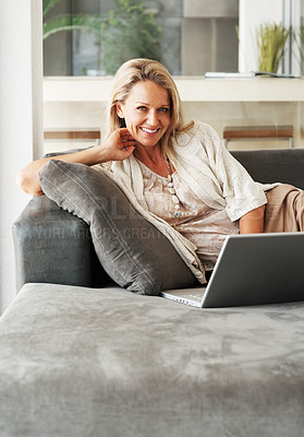 Buy stock photo Portrait of a cheerful middle aged woman lying on sofa while using laptop