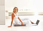 Relaxed mature woman sitting on floor and using laptop