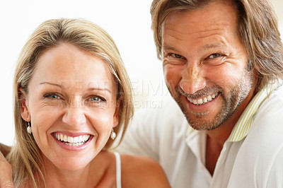 Buy stock photo Closeup portrait of a cute cheerful couple giving you a warm smile against white