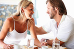 Romantic cheerful couple looking at each other at dining table