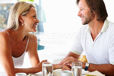 Buy stock photo Portrait of a romantic mature couple looking at each other during breakfast