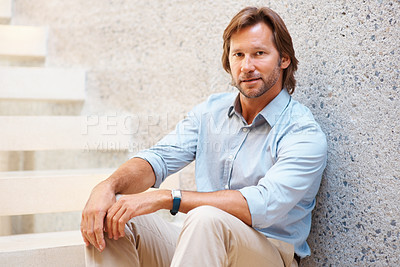 Buy stock photo Portrait of a smart serious mature guy sitting on stairs against wall
