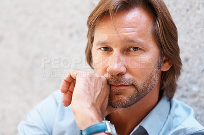 Buy stock photo Closeup portrait of a serious handsome man staring at you with hand on chin