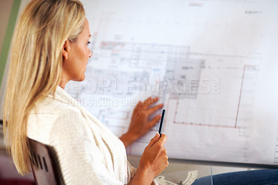 Buy stock photo A female architect working on her construction plans at the office