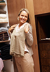 Happy mature female making choices in wardrobe