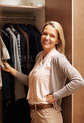 Buy stock photo Portrait of a happy mature woman selecting clothes near wardrobe