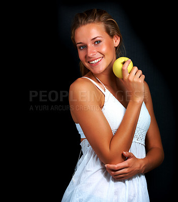 Buy stock photo Portrait of cute young woman holding an apple posing against black background