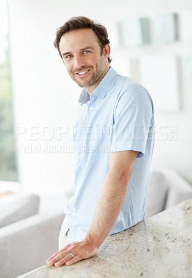 Buy stock photo Portrait of a happy young man standing by kitchen counter- Indoor