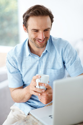 Buy stock photo Portrait of a happy young man holding a cup of tea while looking at the laptop - Indoor