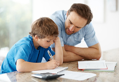 Buy stock photo Portrait of a young man assisting to his little son in schoolwork - Indoor
