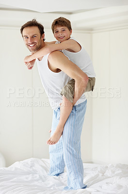 Buy stock photo Portrait of a happy young father piggybacking his son on bed