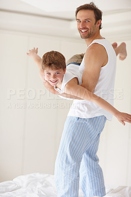 Buy stock photo Portrait of a happy young father playing with his small boy