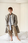 Cute little kid wearing an oversized coat standing on bed