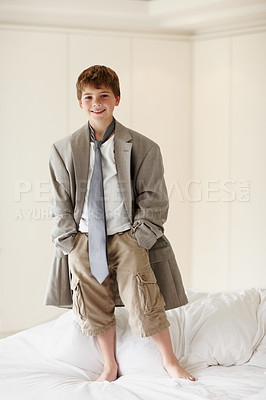Buy stock photo Portrait of a cute little kid wearing an oversized coat standing on bed