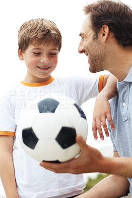 Buy stock photo Portrait of a happy man holding football with his son against bright background
