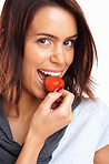 Closeup portrait of a cute female eating a fresh strawberry