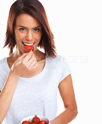 Buy stock photo Happy young female eating a bowl of fresh strawberries against white background
