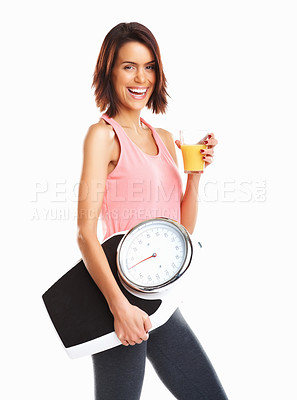 Buy stock photo Thin and beautiful woman standing with glass of juice and a weight scale in her hand, symbol for loosing weight, diet, and healthy nutrition