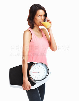 Buy stock photo Symbol for loosing weight - Woman drinking juice with a weight scale in hand