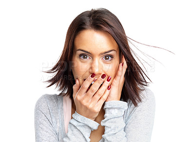 Buy stock photo Portrait of a surprised young woman with hands over her mouth laughing against white background