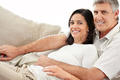 Buy stock photo Portrait of a lovely middle aged couple sitting on couch at home