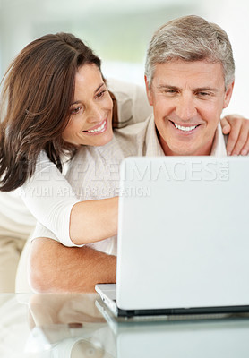 Buy stock photo Portrait of a mature couple browsing the internet on laptop at home
