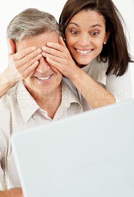 Buy stock photo Portrait of a beautiful woman surprising a mature man working on laptop