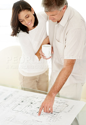 Buy stock photo Portrait of a mature man drinking coffee and showing paperwork to his wife