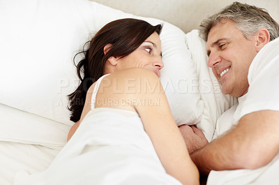 Buy stock photo Portrait of a mature couple looking at each other while lying on bed smiling