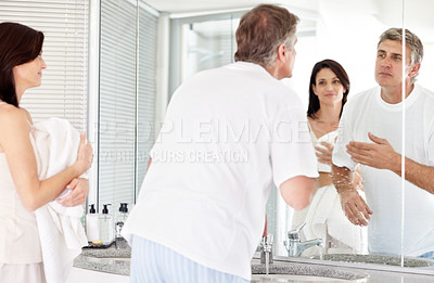 Buy stock photo Portrait of mature man in washroom looking in mirror while his wife holding towel