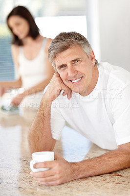 Buy stock photo Portrait of handsome mature man drinking coffee with his wife standing in background