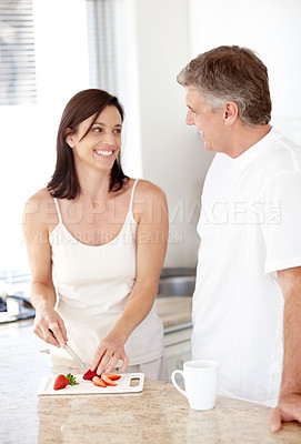 Buy stock photo Portrait of  happy mature lady cutting fresh fruit with her husband