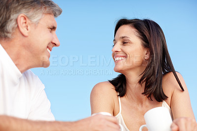 Buy stock photo Portrait of happy mature couple having coffee together against sky