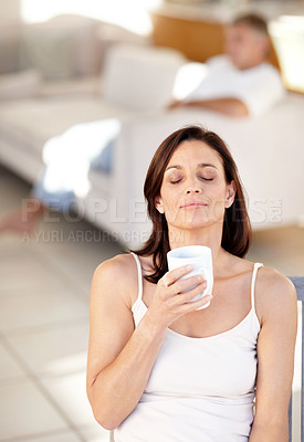 Buy stock photo Portrait of a lovely mature woman holding a cup of  coffee with her husband in background