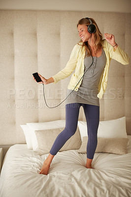 Buy stock photo Portrait of a pretty young female enjoying listening to music while dancing on her bed at home