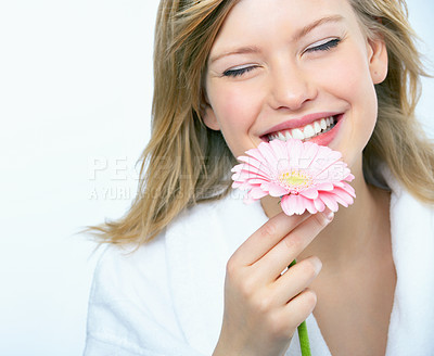 Buy stock photo Young woman holding a flower, smelling it and smiling with her eyes closed