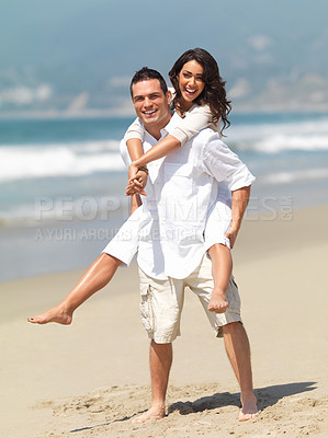 Buy stock photo Portrait of a young man piggybacking his girlfriend on a beach
