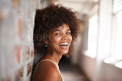 Buy stock photo Cropped portrait of an attractive young woman leaning against a brick wall
